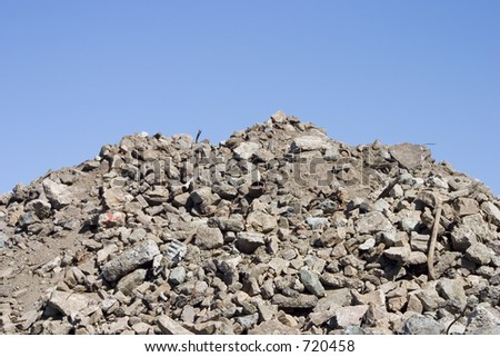 A pile of dirt and busted-up rubble at a construction site. - stock photo