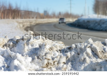 A pile of dirty snow on the side of the road - stock photo