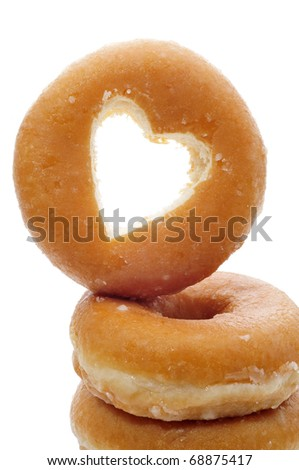 a pile of donuts one with the hole shaped as a heart on a white background - stock photo