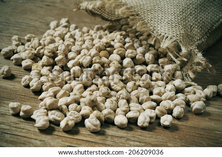 a pile of dried chickpeas on a rustic wooden table - stock photo