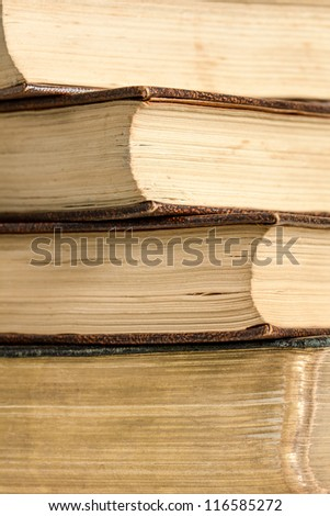 A pile of four antique books showing aging of the pages. Vertical format and whilst the subject fills the frame, there is space for copy. - stock photo