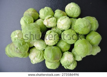 A pile of fresh green Brussels sprouts on dark surface. Healthy/clean eating concept; organic/unprocessed food; paleo diet. - stock photo