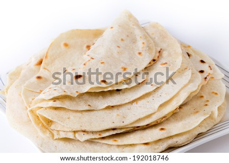 A pile of fresh homemade wheat tortillas on a plate.