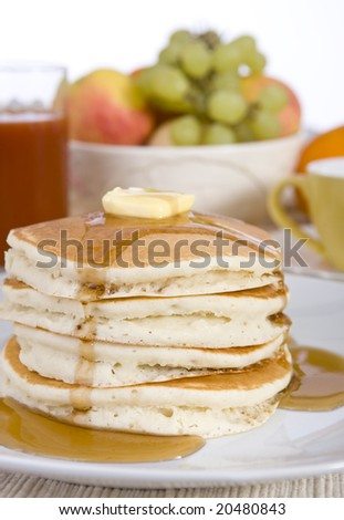 A pile of fresh pancakes with melted butter and syrup.