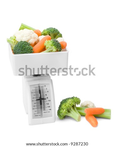 A pile of fresh vegetables on a food scale.