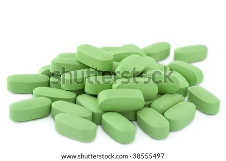 A pile of green multi-vitamine pills. Isolated on white background.