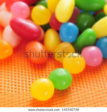 a pile of jelly beans of different colors on an orange woven background