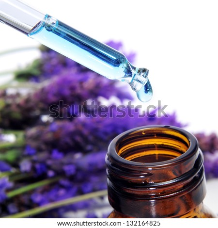 a pile of lavender flowers and a dropper bottle with lavender essence