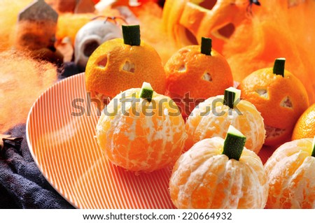 a pile of mandarines ornamented as Halloween pumpkins with scary ornaments in the background, such as skulls, spiders and spider web - stock photo