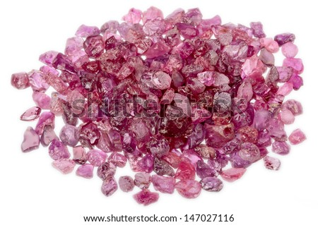 A pile of natural, uncut, raw and rough rubies in red and pink isolated on white.