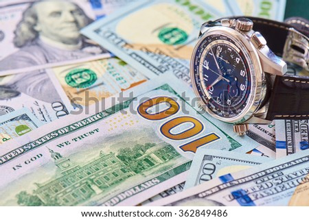 A pile of new one hundred US dollars banknotes and luxury watch close up or background.