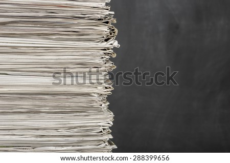 A pile of newspapers in front of a chalkboard - stock photo