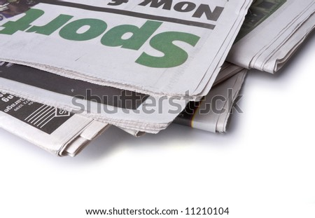 A pile of newspapers isolated on white. The sports pages are at the top of the pile. See more newspaper images in my gallery.