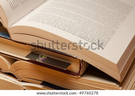 A pile of old books closeup, some opened. - stock photo