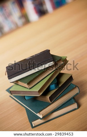 A pile of old books on a table. Shot at an angle. - stock photo