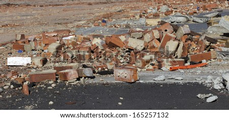 A pile of old broken  red clay brick rubble after demolition of an old building  lies on the ground  on a building  site. - stock photo
