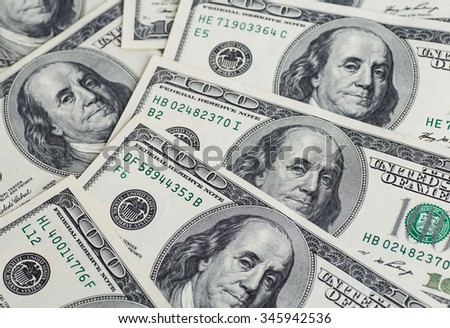 A pile of one hundred US dollar bills on a table - stock photo