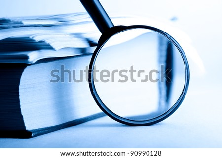 A pile of paper and a book through the magnifying glass - stock photo