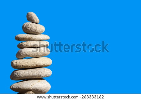 A pile of pebbles on a rock in front of blue sky background. - stock photo
