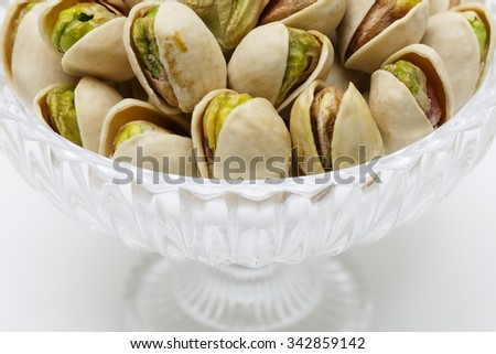 A pile of pistachio in a glass cup.
