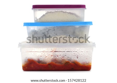 a pile of plastic containers with food on a white background - stock photo
