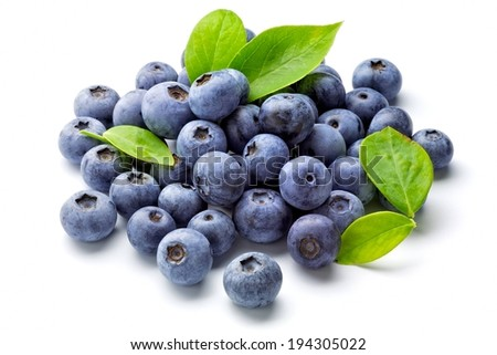 A pile of ripe blueberries, with a few green leaves. - stock photo