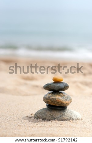 A pile of round smooth zen rocks stacked in the sand at the beach. - stock photo