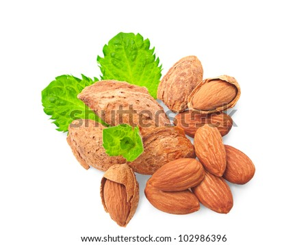 A pile of shelled and un-shelled almonds, with a sprig of mint. On a white background. - stock photo