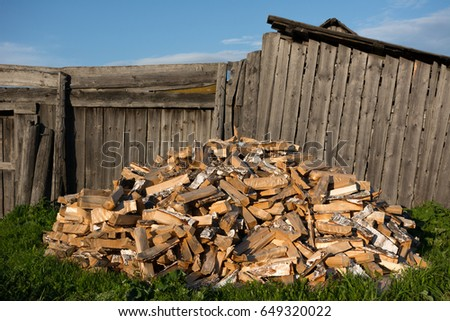 a pile of split birch firewood near an old wooden fence