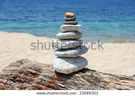 a pile of stones on a rock, the blue sea and the beach in the background - stock photo