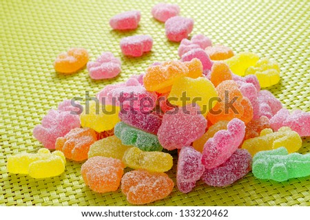 a pile of sugar coated candies of different colors on a green woven background - stock photo