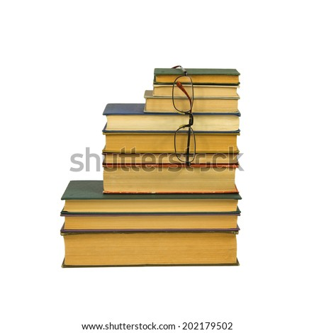 A pile of the old books and glasses isolated on white background