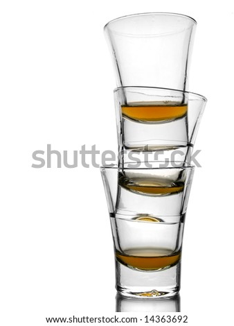 A pile of three almost empty shots of whiskey on white background with reflex. - stock photo
