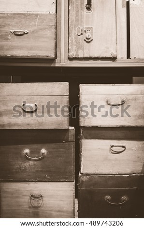 A pile of vintage, old-fashioned wooden boxes and suitcases. Sepia tone.