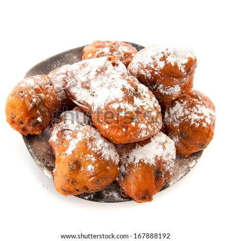 a pile with oliebollen on a plate on a white background - stock photo