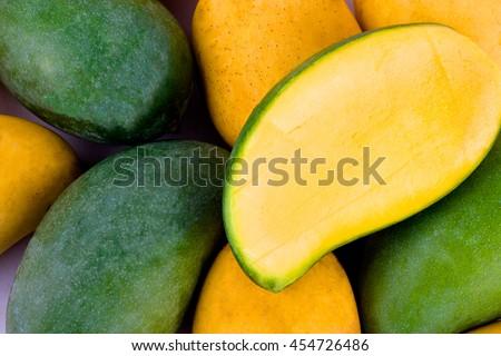 a pile yellow ripe mango and fresh green mango and half mango  on white background healthy fruit food isolated  - stock photo