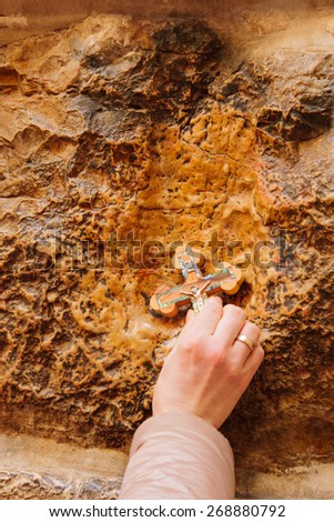 A pilgrim blesses a cross with Jesus hand print, in Via Dolorosa station 5, on Orthodox Good Friday, in the old city of Jerusalem, Israel - stock photo