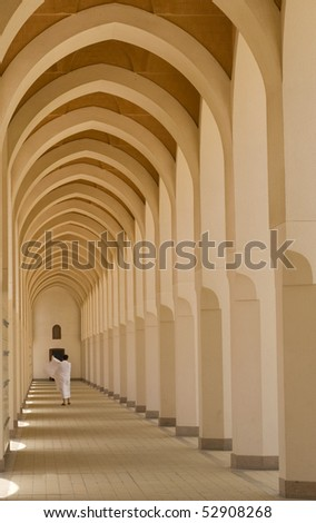 A pilgrim in 'ihram' cloth walks down a walkway in Medina. 'Ihram' clothes consist of two unhemmed white clothes intended to make everyone appears the same. - stock photo