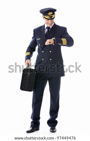 A pilot with a suitcase looking at the clock on a white background