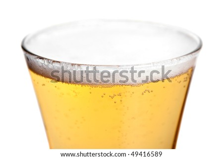 A pilsner glass with golden lager beer isolated over white.  Shallow depth of field. - stock photo