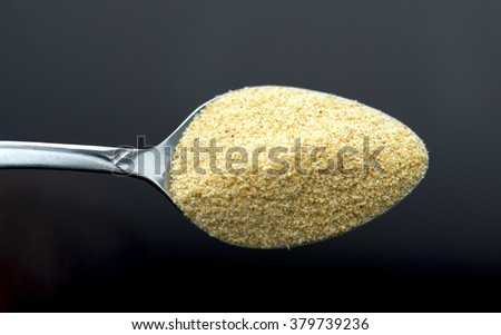 A pinch of small granulated garlic on a spoon - stock photo