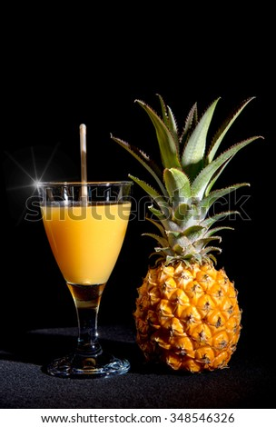 a pineapple juice with fruit on black background - stock photo