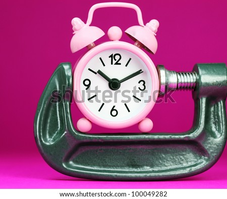 A pink alarm clock placed in a Grey clamp against a pastel purple background, asking the question do you manage your time effectively. - stock photo
