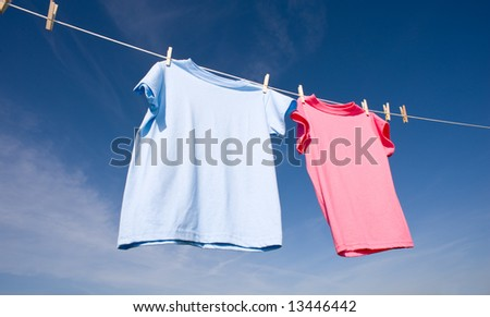 a pink and a baby blue T-shirt hanging on a clothesline on a beautiful, sunny day, add text or graphic to shirts or copy space - stock photo