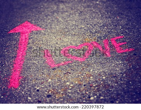 a pink arrow showing the way to love written on a sidewalk with chalk toned with a retro vintage instagram filter effect (very shallow depth of field)  - stock photo