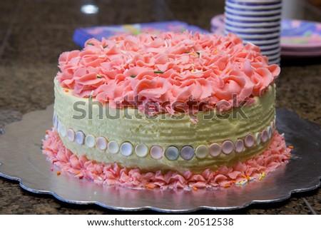 a pink birthday cake closeup on granite counter top - stock photo