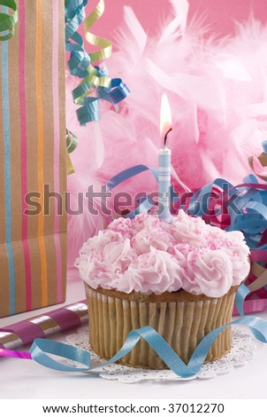 A pink birthday cupcake with one blue lit candle, low key, vertical with colorful gift bag, copy space