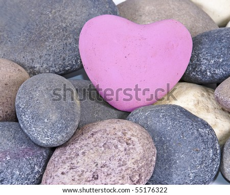 a Pink coloured stone heart surounded by other natural stones - stock photo