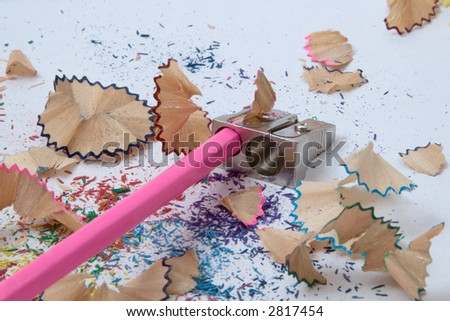 A pink crayon under sharpening on pencil shavings