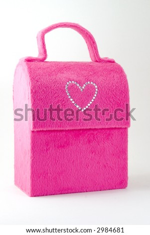 A pink fur covered bag with a diamond heart motif